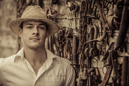 agronomist: Farmer Portrait in front of a Wall Full with Old Rusty Tools Stock Photo