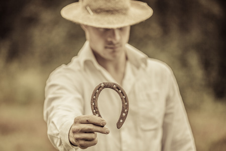 agronomist: Lucky Farmer Holding a Horseshoe in his right hand