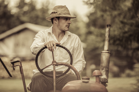 old tractors: Young Farmer Driving a Red Old Vintage Tractor Stock Photo