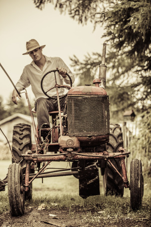 Young Farmer Driving a Red Old Vintage Tractor Stockfoto