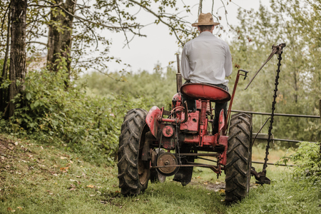 agronomist: Young Farmer Driving a Red Old Vintage Tractor Stock Photo