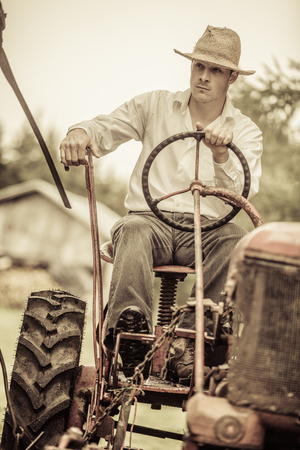 Young Farmer Driving a Red Old Vintage Tractor Stock Photo