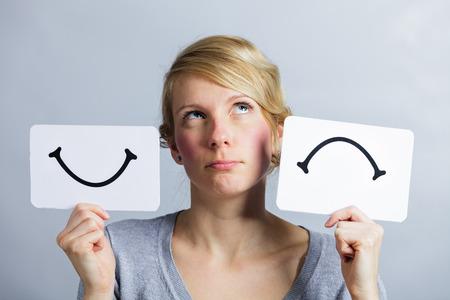 Porträt einer Befragung Woman Holding glückliche und unglückliche Umfrage Moodboard