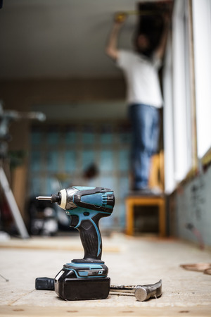 cordless: Battery Drill on the Floor with Worker in Background