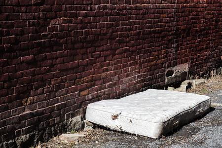 vagabundos: Colchón abandonado viejo y sucio en un Backstreet