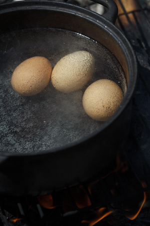 Eggs in a Cast Cauldron full Boiling Water on a Camping Fire photo