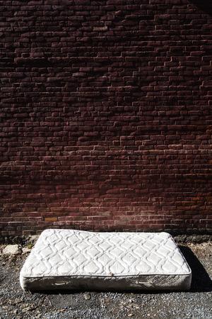 broken wall: Colchón abandonado viejo y sucio en un Backstreet