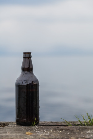 microbrewery: Opened 500ml Bottle of Beer on old Rustic Wood in nature