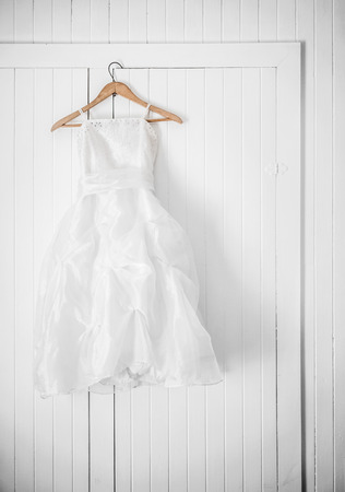 Classic Flower Girl Dress Hanging on a White Wall Stock Photo