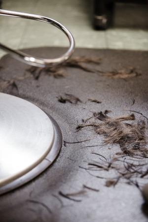 barbershop: Hair Salon Chair Closeup with Hairs On the Floor Stock Photo