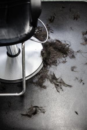 Hair Salon Chair Closeup with Hairs On the Floor Фото со стока