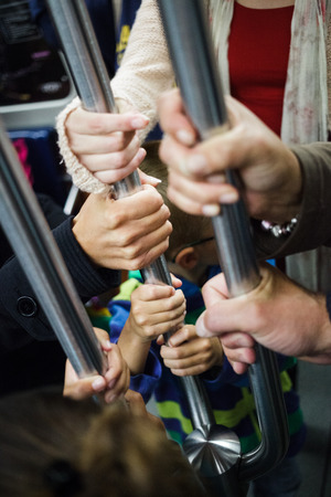Lot of Hands Holding at the same Pole in a Subway Wagon