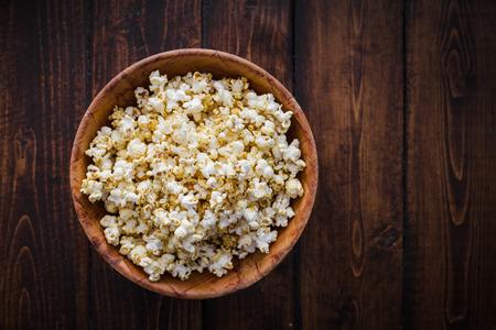 Gekruide Popcorn in een houten kom op een tafel in de woonkamer Stockfoto