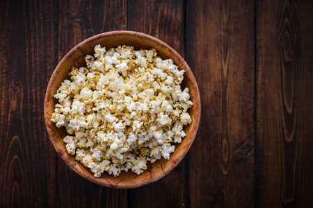 eating popcorn: Spiced Popcorn in a Wooden Bowl on a Table in the Living Room