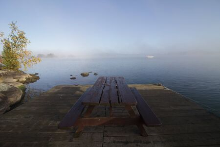Picnic Table with No People on a Dock During a Foggy Calm Morning Stock Photo