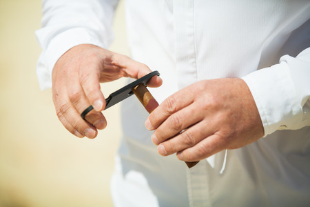 cutter: Man Cutting a Cigar Using Straight Cut with Double-Guillotine Cutter Stock Photo