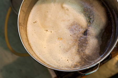 fermenting: Froth of Home-Brew Mash in a Stock Pot While Sparging the water to Drain the Sugar Stock Photo