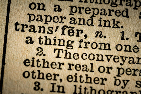 transfering: October 6th, 2015 - Montreal, Canada. Old 1945 Websters Dictionary Macro Close-up of the word TRANSFER and its definition on old textured yellow paper.