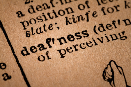 deafness: October 1st, 2015 - Montreal, Canada. Close-up of an Old 1945 Webster Vintage Dictionary showing the Word Deafness