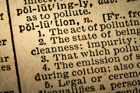 October 6th, 2015 - Montreal, Canada. Old 1945 Websters Dictionary Macro Close-up of the word POLLUTION and its definition on old textured yellow paper.