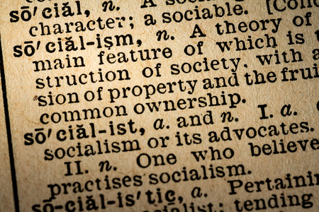 socialism: October 6th, 2015 - Montreal, Canada. Old 1945 Websters Dictionary Macro Close-up of the word SOCIALISM and its definition on old textured yellow paper.