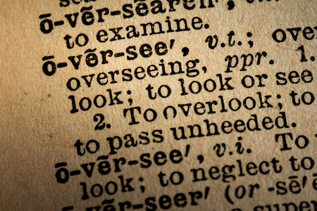 oversee: October 6th, 2015 - Montreal, Canada. Old 1945 Websters Dictionary Macro Close-up of the word OVERSEE and its definition on old textured yellow paper.