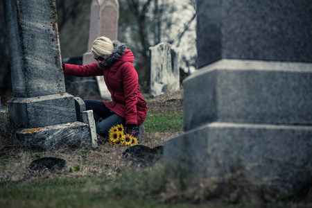 Lonely Sad Young Woman in Mourning with Sunflowers Touching a loved one's Gravestone in a Cemetery