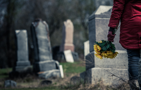 grieve: Close-up of a Sad Woman Holding Sunflowers in front of a Loved ones Gravestone. Focus on the Bouquet.