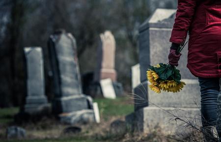 Zbliżenie smutnej kobiety trzymającej Słoneczniki przed bliskiej osoby za grób. Skoncentruj się na bukiet.