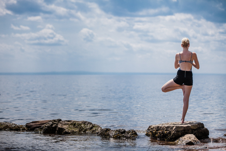 tree position: Young Woman doing Yoga Tree Position in Front of the Ocean Stock Photo