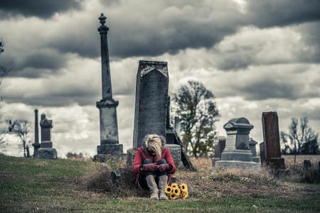 luto: Solo triste mujer joven en duelo con los girasoles en frente de una lápida en un cementerio