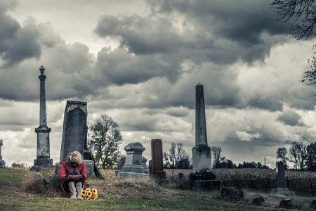 grieve: Lonely Sad Young Woman in Mourning with Sunflowers in front of a Gravestone in a Cemetery
