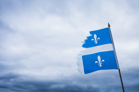 lacerate: Strong Metaphor using a Broken Quebec Flag and a Sad Sky. Stock Photo