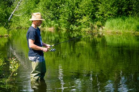 paciencia: Pescador joven de pesca con paciencia en un arroyo de agua dulce