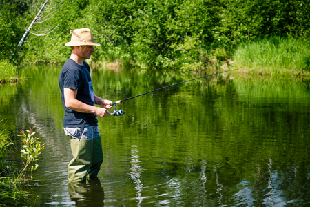 freshwater: Young Fisherman Fishing with Patience into a Freshwater creek