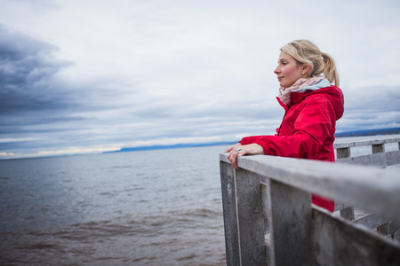 cloudy day: Lonely Young Woman Looking a the View of the Ocean from an Observatory During a cold Autumn Cloudy Day Stock Photo