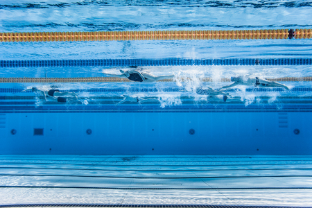 swimmer: Underwater view of Unrecognizable Professional Swimmers Training into a 50m Outdoor Pool Stock Photo
