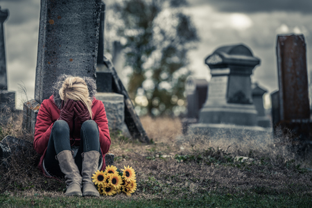 christian religion: Lonely Crying Young Woman in Mourning with Sunflowers in front of a Gravestone in a Cemetery