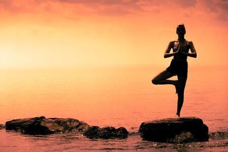 tree position: Young Woman doing the Tree Yoga Position in Front of the Ocean During Sunset Stock Photo