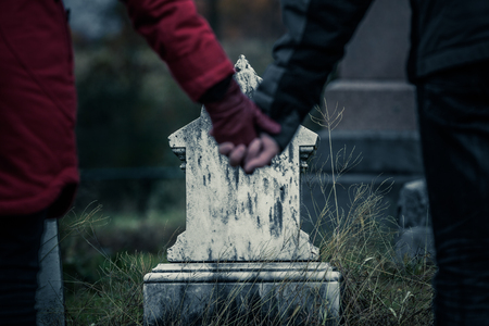 grave: Couple or Brother and Sister Holding Hands in front of a small Gravestone. Lost of a Loved one is never easy. Stock Photo