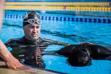 freediving: Montreal, CANADA - May 30th, 2015. Official AIDA Freediving Pool Competition Taking place in the Parc Jean-Drapeau Olympic Pool. Coach Doing the Safety and Watching the Performer doing Static Apnea. Editorial