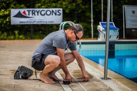 piscina olimpica: Montreal, Canadá - 30 de mayo de 2015. Oficial AIDA Apnea piscina Competencia lugar Tomando en el Parque Jean-Drapeau piscina olímpica. Miembro del personal de colocar la cinta en el lado de la piscina para la medición. Editorial