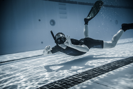 freediving: Montreal, CANADA - May 30th, 2015. Official AIDA Freediving Pool Competition Taking place in the Parc Jean-Drapeau Olympic Pool. Safety Staff member Having fun Underwater Between two Performances. Editorial