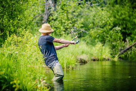 freshwater: Young Fisherman Catching a big Fish into a Freshwater creek