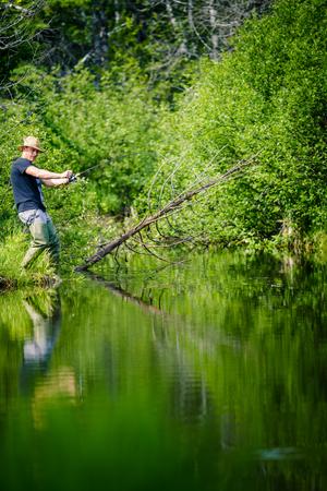 the big fish: Young Fisherman Catching a big Fish into a Freshwater creek