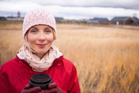 Gelukkig knappe vrouw in een veld tijdens de koude herfst dag met een kopje koffie