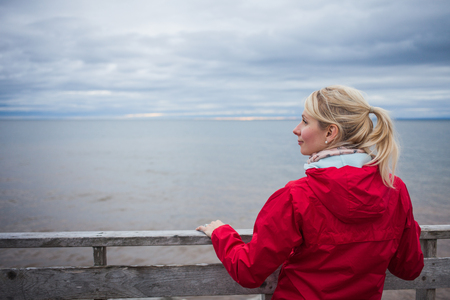 guard rail: Lonely Young Woman Looking a the View of the Ocean from an Observatory During a cold Autumn Cloudy Day Stock Photo