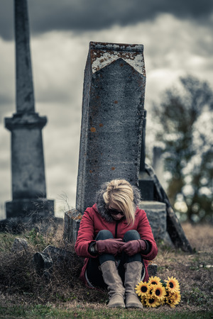 grave: Lonely Sad Young Woman in Mourning with Sunflowers in front of a Gravestone in a Cemetery