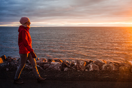 winter sunrise: Young Woman Walking on the Beach during Sunset on a Cold Evening Stock Photo