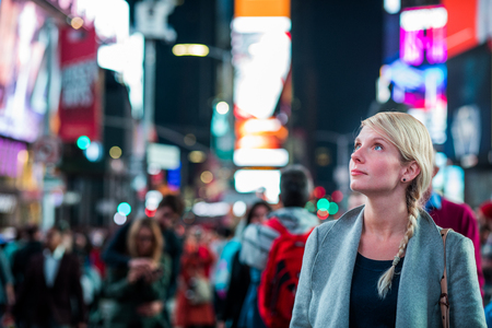 Impressed Woman in the Middle of Times Square at Night, Reklamní fotografie - 82500611